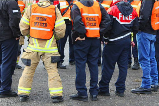 First responders in orange vests standing in a circle having a discussion at a mass violence drill