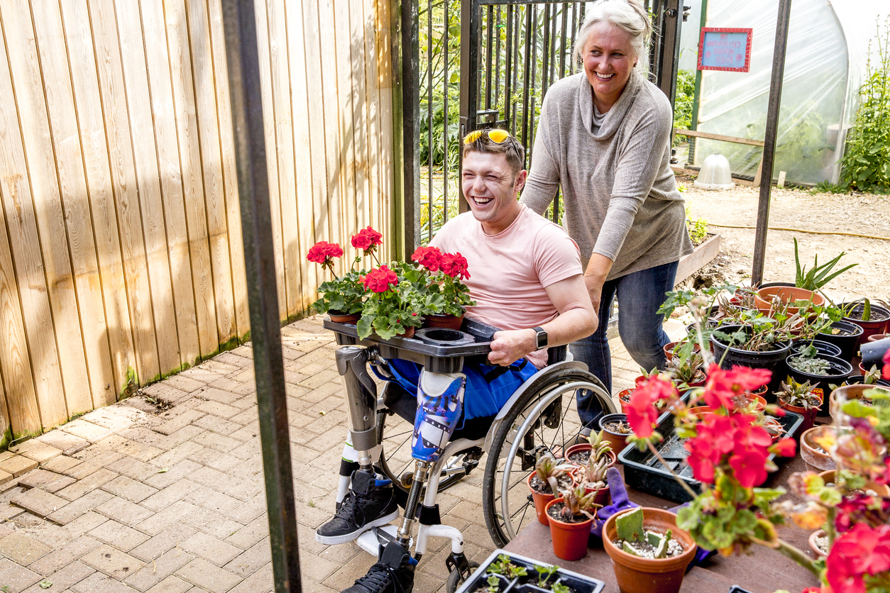 Woman pushing a young, male mass violence survivor with prosthetic legs in a wheelchair at a Greenhouse